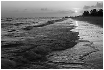 Beach with people in the distance at sunset, Sanibel Island. Florida, USA ( black and white)
