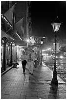 People on sidewalk of River Street by night. Savannah, Georgia, USA ( black and white)