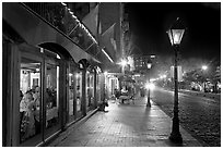 Restaurant, lamps, and sidewalk of River Street by night. Savannah, Georgia, USA (black and white)