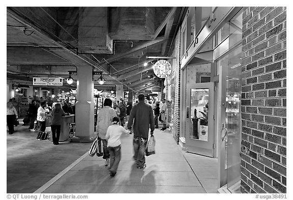 Family walking in front of Underground Atlanta store with historic brick wall. Atlanta, Georgia, USA (black and white)