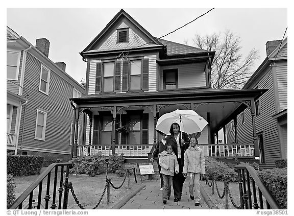 African American family with umbrella in front of Birth Home of Martin Luther King Jr. Atlanta, Georgia, USA (black and white)