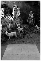 Tombstone of a French priest, and figures inside a replica of the Lourdes grotto, church Saint-Martin-de-Tours, Saint Martinville. Louisiana, USA (black and white)