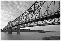 Barge on the Mississippi River approaching bridges. Natchez, Mississippi, USA (black and white)