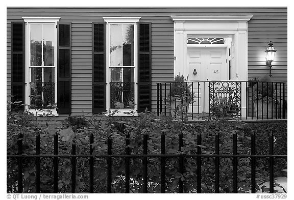 House facade at dusk with roses in front yard. Charleston, South Carolina, USA (black and white)