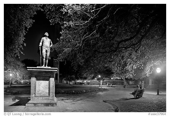 Park with statue and couples sitting on public benches at night. Charleston, South Carolina, USA