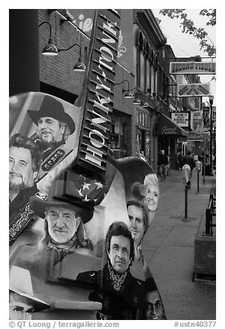 Guitar-shaped sign with images of famous singers on Broadway sidewalk. Nashville, Tennessee, USA (black and white)