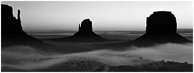 Monument Valley mittens at sunrise with fog. Monument Valley Tribal Park, Navajo Nation, Arizona and Utah, USA (Panoramic black and white)