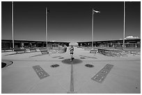 Woman straddling the territory of four states. Four Corners Monument, Arizona, USA (black and white)