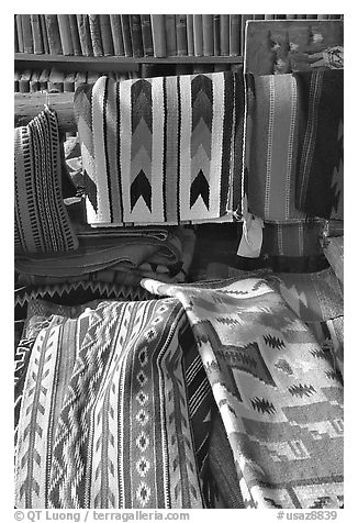 Stacks of varicolored blankets and rugs weaved by Navajo Indians. Hubbell Trading Post National Historical Site, Arizona, USA (black and white)