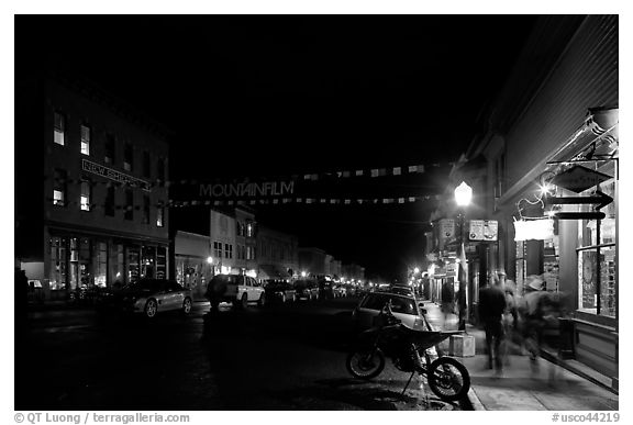 People walking by store on Colorado Street by night. Telluride, Colorado, USA (black and white)