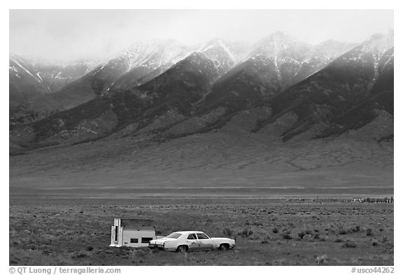 Car and pickup cover below snowy peaks. Colorado, USA (black and white)