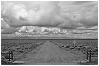 Cattle guard and straight dirt road. Colorado, USA (black and white)