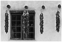 Yellow wall with ristras and blue window. Taos, New Mexico, USA ( black and white)