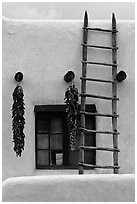 Strings of red peppers and ladder on building in pueblo style. Taos, New Mexico, USA ( black and white)