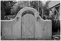 Blue door and adobe yard wall. Taos, New Mexico, USA (black and white)