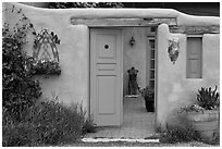 Adobe style walls, blue doors and windows, and courtyard. Taos, New Mexico, USA ( black and white)