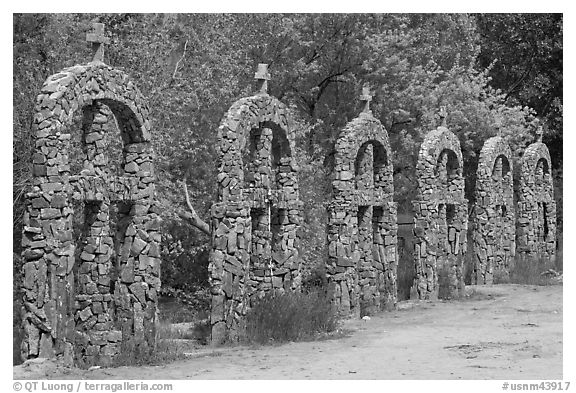 Brick and stone crosses by the river, Sanctuario de Chimayo. New Mexico, USA (black and white)