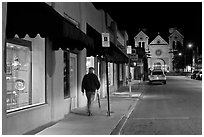 Man walking gallery and St Francis by night. Santa Fe, New Mexico, USA ( black and white)