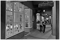 Couple walking by night in front of gallery. Santa Fe, New Mexico, USA ( black and white)