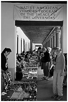 Tourists browse wares sold under native american vendors program of the palace of the governors. Santa Fe, New Mexico, USA (black and white)