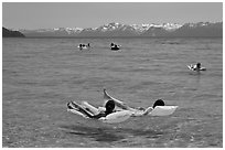 Children playing in water, and distant snowy mountains, Sand Harbor, Lake Tahoe, Nevada. USA (black and white)
