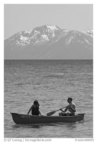 Man and woman in canoe with snowy mountains in the background, Lake Tahoe, Nevada. USA (black and white)