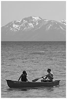 Man and woman in canoe with snowy mountains in the background, Lake Tahoe, Nevada. USA ( black and white)