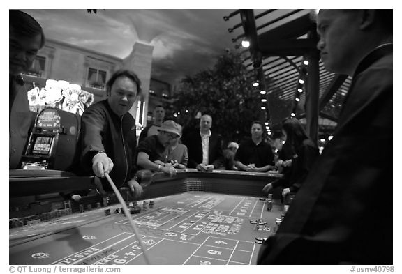 Dealer collecting during Craps game. Las Vegas, Nevada, USA (black and white)