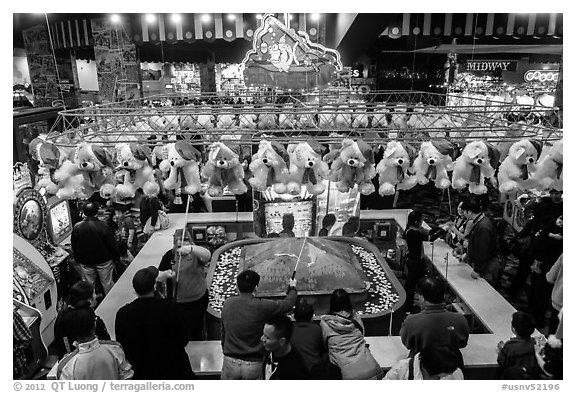 View from above of people playing carnival fishing game. Reno, Nevada, USA (black and white)