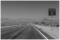 Highway and Next Gas 163 miles sign. Nevada, USA (black and white)