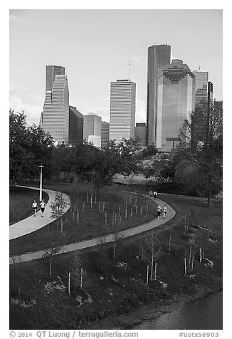 People walking in park with skyline behind. Houston, Texas, USA (black and white)