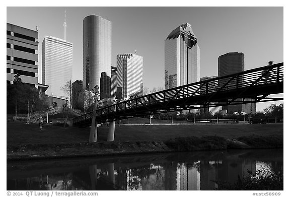 Bridge with bicyclist, reflection, and skyline. Houston, Texas, USA (black and white)