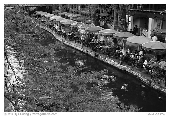 Tables under colorful umbrellas next to canal. San Antonio, Texas, USA (black and white)