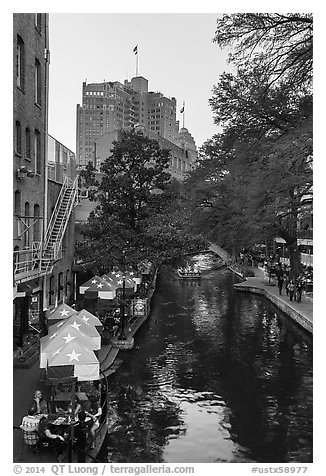 Riverwalk promenade, approaching barge. San Antonio, Texas, USA (black and white)