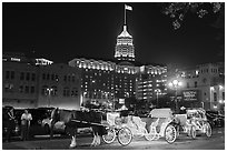 Horse carriages and Tower Life Building at night. San Antonio, Texas, USA ( black and white)