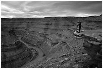 Photographer on overhang above the San Juan River, Goosenecks of the San Juan State Park. Utah, USA (black and white)