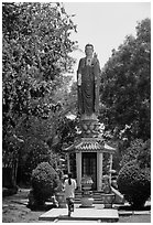 Woman praying under a large buddhist statue. Ho Chi Minh City, Vietnam ( black and white)