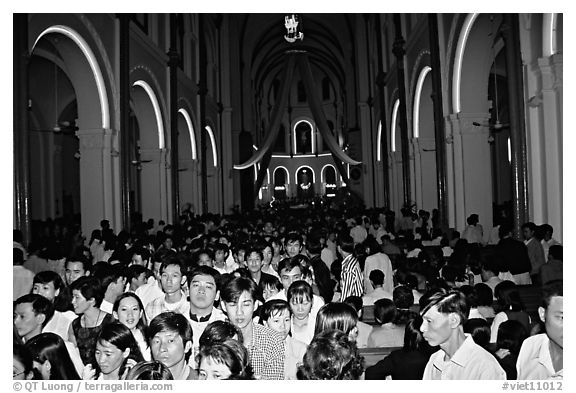 Crowds exit the Cathedral St Joseph at the end of the Christmas mass. Ho Chi Minh City, Vietnam (black and white)