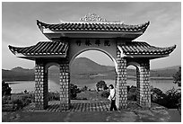 Pagoda gate with woman standing near lake. Da Lat, Vietnam ( black and white)