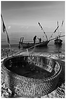 Fishermen pulling net out of circular basket. Phu Quoc Island, Vietnam (black and white)
