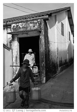 Workers carrying out containers of nuoc mam, Duong Dong. Phu Quoc Island, Vietnam (black and white)