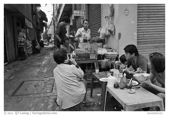Breakfast at food stall in alley. Ho Chi Minh City, Vietnam (black and white)