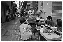 Breakfast at food stall in alley. Ho Chi Minh City, Vietnam ( black and white)