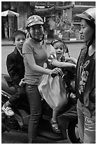 Woman riding with children. Ho Chi Minh City, Vietnam (black and white)
