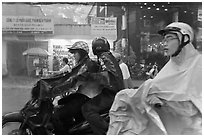 Motorcycle riders during afternoon mooson. Ho Chi Minh City, Vietnam ( black and white)