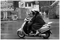 Women ride motorcycle in the rain. Ho Chi Minh City, Vietnam (black and white)