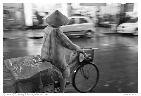 Woman rides bicycle in the rain. Ho Chi Minh City, Vietnam (black and white)