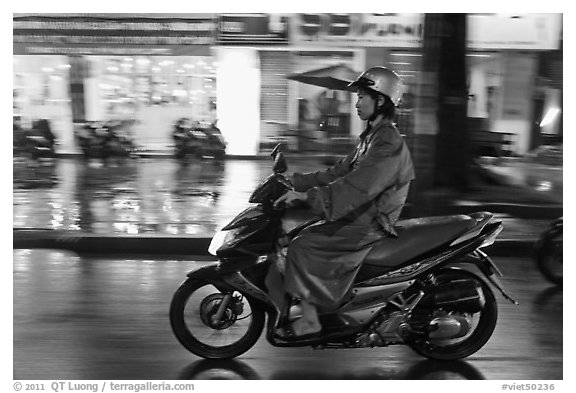 Riding motorcyle on rainy night. Ho Chi Minh City, Vietnam (black and white)
