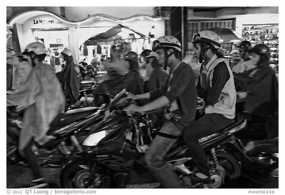 Street crowded with motorcycles on rainy night. Ho Chi Minh City, Vietnam (black and white)