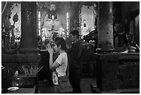 Couple worshipping Thang Hoang, Chua Ngoc Hoang pagoda, district 3. Ho Chi Minh City, Vietnam ( black and white)